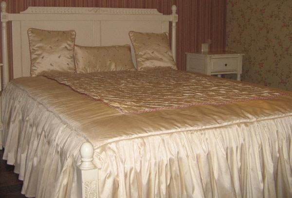Атласное покрывало сшитое из рюшек по краю и стеганного элемента в центре, выглядит как украшение вашей спальни.
